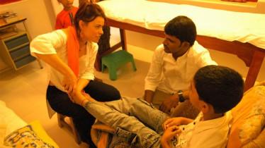 Marie masse les pieds d'un petit garçon qui souffre d'une angine